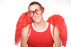 Young man smiles in red heart-glasses with wings o Stock Photography