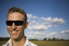 Young man smiling. Cool young man with sunglasses smiling. Sunny summer setting with few clouds. Extremely narrow depth of field stock photo