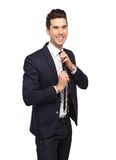 Young man smiling and adjusting necktie Royalty Free Stock Photography