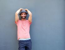 Young man smiling against gray background with hat Royalty Free Stock Photos