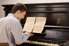 Young man smiling as he plays the piano. View from the rear of a young man smiling as he plays the piano using an old vintage music score on an upright wooden Stock Photography