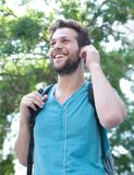 Young man smiling with backpack and earphones outdoors Stock Photos