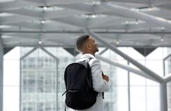 Young man smiling with bag at airport Stock Photos