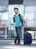 Young man smiling with bags at airport Stock Image