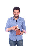 Young man smiling. Smiling beard young man feeling happy and opening a brown gift, guy wearing blue shirt and jeans, isolated on white background Royalty Free Stock Photos
