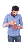 Young man smiling. Smiling beard young man opening a brown gift and looking down, guy wearing blue shirt and jeans, isolated on white background Royalty Free Stock Photography