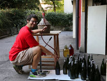 Young man smiling while bottling the wine at home Stock Images