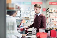 Young man smiling while buying an useful pharmaceutical product. Portrait of a handsome young men smiling while buying an useful pharmaceutical product in a Royalty Free Stock Image