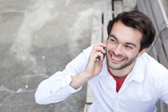 Young man smiling and calling by mobile phone outdoors. Close up portrait of a young man smiling and calling by mobile phone outdoors Stock Photography