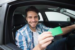 Young man smiling at camera showing card Royalty Free Stock Photo