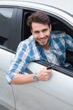 Young man smiling at camera showing key Royalty Free Stock Image