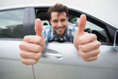 Young man smiling at camera showing thumbs up Stock Images