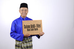 Young man smiling with chalkboard for Eid Fitr or Eid Adha celeb Stock Photos
