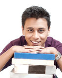 Young Man Smiling with Chin on Books Royalty Free Stock Photo