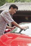 Young Man Smiling and Cleaning His Car Royalty Free Stock Photos