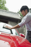 Young Man Smiling  and Cleaning His Car Royalty Free Stock Photo