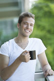 Young man smiling with coffee Stock Photography