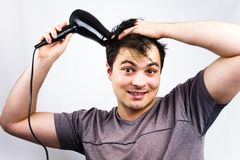 Young man smiling while he dries his hair. Teenager holding hair electric fan. Young man dries hair with an electric fan. Preparin. G a hair for going to a night Stock Photos