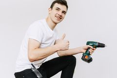 Young man smiling with the drill or screwdriver isolated on white background stock image