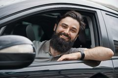 Young man smiling while driving a car Stock Images