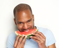 Young man smiling and eating delicious watermelon. Portrait of a young man smiling and eating delicious watermelon against white background Stock Photography