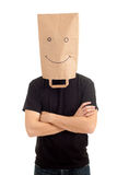 Young man in smiling ecological paper bag on head Stock Photography