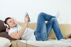 Young man smiling enjoying music with headset and cellphone Stock Photos