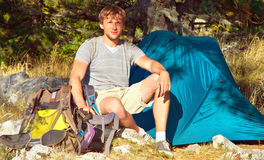 Young Man with Smiling Face Hiker sitting with backpack and Tent Camping Outdoor Stock Photography