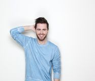 Young man smiling with hand in hair Stock Photography