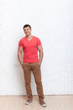 Young Man Smiling Hands In Pocket Stand Over Wall Stock Photo