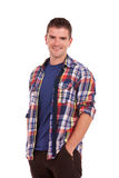 Young man smiling with hands in pockets. Portrait of a casual young man smiling with his hands in his pockets against white background Royalty Free Stock Photos