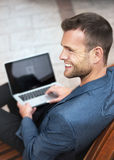 Young Man Smiling with his Laptop Royalty Free Stock Images