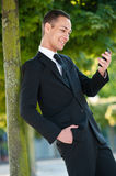 Young Man Smiling at his Phone in Park Royalty Free Stock Photography