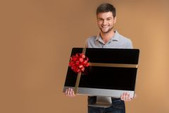 Young man smiling and holding big tv screen. stock photography
