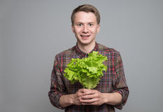 Young man smiling. Smiling young man holding green lettuce on grey background Royalty Free Stock Photos