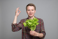 Young man smiling. Smiling young man holding green lettuce and showing ok sign on grey background Stock Photo