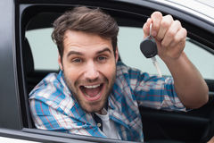 Young man smiling and holding key Royalty Free Stock Photo