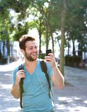 Young man smiling and holding mobile phone. Portrait of a young man smiling and holding mobile phone Royalty Free Stock Image