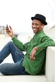 Young man smiling holding mobile phone. Portrait of a young man smiling holding mobile phone with earphones Stock Photo