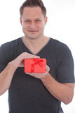 Young man smiling while holding a red gift box Royalty Free Stock Photos