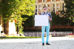 Young man smiling and holding a white cardboard Stock Image