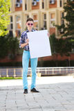 Young man smiling and holding a white cardboard Royalty Free Stock Photos
