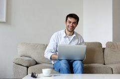 Young man smiling with laptop at home Royalty Free Stock Image
