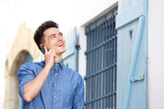 Young man smiling and listening to cell phone Royalty Free Stock Images