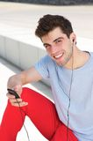 Young man smiling and listening to his mp3 player outdoors Stock Photography