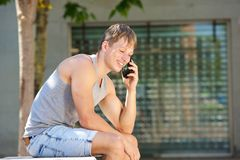 Young man smiling and listening to mobile phone call Stock Photo