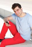 Young man smiling and listening to music on mp3 player Stock Photo