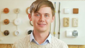 A young man smiling and looking at camera on the background of sockets and switches. Seller is dressed in a shirt and stock video footage