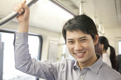 Young man smiling and looking at camera in subway Stock Image