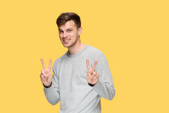 The young man smiling and looking at camera. On yellow studio background Royalty Free Stock Images